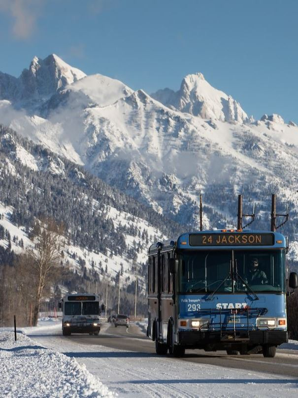 START buses driving on 22 in Winter with Tetons in background